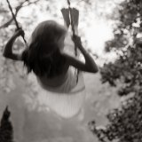 black and white photo of girl swinging